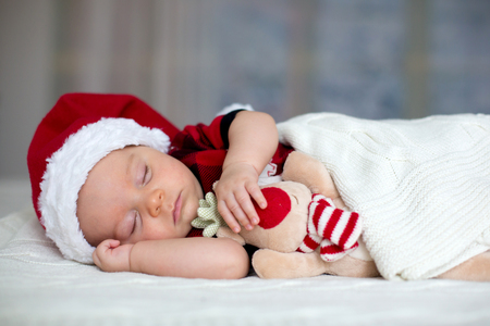 Little sleeping newborn baby boy, wearing Santa hat and jeans, holding toy Stockfoto