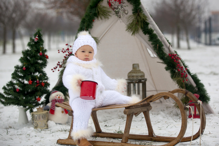 Happy family with kids, having fun outdoor in the snow on Christmas, playing with sledge, teepee and christmas decoration