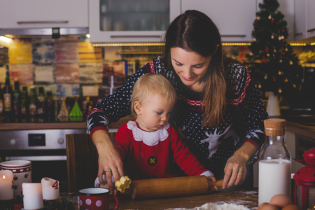 Sweet toddler child, boy, helping mommy preparing Christmas cookies at home in kitchen Banco de Imagens