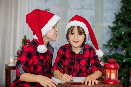 Two adorable children, boy brothers, writing letter to Santa Claus at home 写真素材