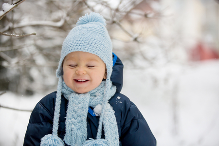 Cute little toddler boy, playing outdoors with snow on a winter day, snowing Stockfoto