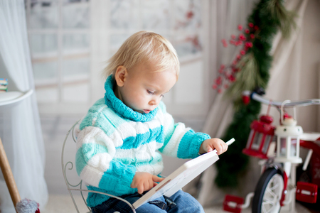 Cute little toddler child with colorful book at home on a snowy winter day, christmas decoration Stock Photo