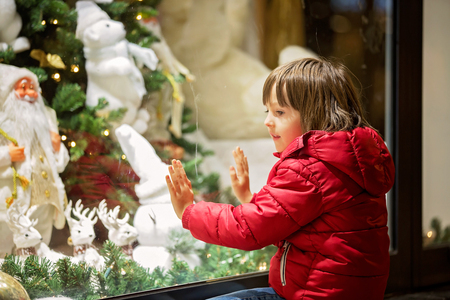 Beautiful little child, boy, watching Christmas decoration with toys in a shop window display, wishing for a present, his reflection in the window Stok Fotoğraf - 114347807