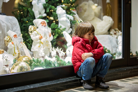 Beautiful little child, boy, watching Christmas decoration with toys in a shop window display, wishing for a present, his reflection in the window