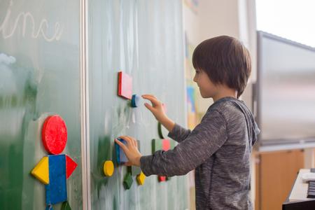 Niño de primer grado, aprendiendo matemáticas, formas y colores en la escuela, de pie frente a la pizarra