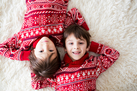 Happy brothers, baby and preschool children, hugging at home on white blanket, smiling, shot from above Stock fotó