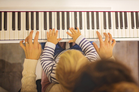 Sweet positive toddler child and mother playing piano. Early music education for little kids, children at home learning music instruments
