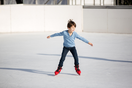 Happy boy with hat and jacket, skating during the day, having fun outdoors, winter time on Christmas Stock Photo