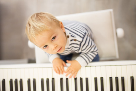Sweet positive toddler child playing piano. Early music education for little kids, children at school, learning music instruments