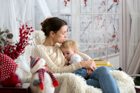 Mother breastfeeding her toddler son sitting in cozy armchair, snowing outside wintertime