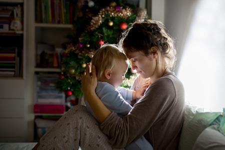 Young beautiful mother, breastfeeding her newborn baby boy at night, dim light. Mom breastfeeding toddler on Christmas