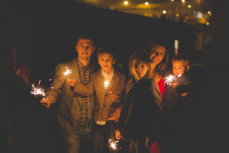 Waist up portrait of happy family celebrating New Year together and lighting sparklers outdoors in garden