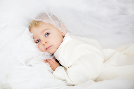 Portrait of elegant handsome little boy in a tuxedo, lying in bed on his moms bridal dress, ready to go to wedding