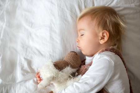 Sweet baby boy in cute overall, sleeping in bed with teddy bear stuffed toys, winter landscape behind him Stock Photo