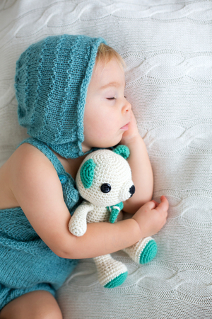 Sweet toddler boy, sleeping with teddy bear toy, cute knitted outfit, isolated Banco de Imagens - 116350303