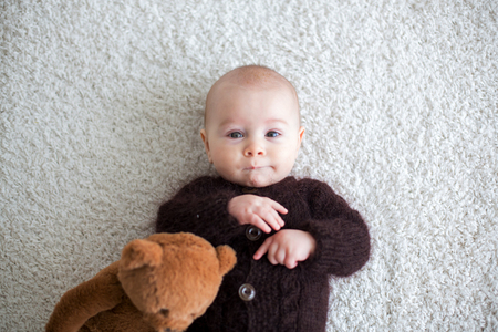 Little cute baby boy, dressed in handmade knitted brown teddy bear overall, playing at home in sunny bedroom
