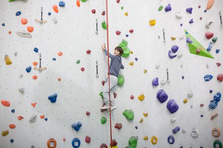Sweet little preschool boy, climbing wall indoors, having fun, active children