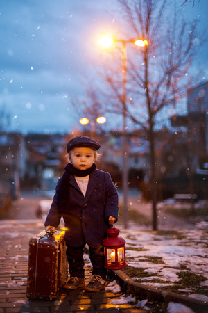 Toddler boy, standing on stairs, holding lantern and old suitcase, street view of Prague behind him, snowy evening Stockfoto
