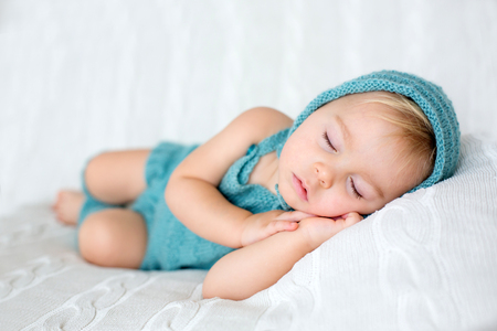 Sweet toddler boy, sleeping with teddy bear toy, cute knitted outfit, isolated Фото со стока - 116350648