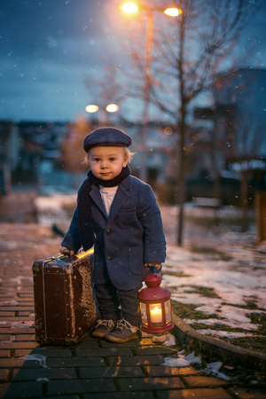 Toddler boy, standing on stairs, holding lantern and old suitcase, street view of Prague behind him, snowy evening Stock Photo