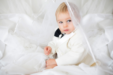 Portrait of elegant handsome little boy in a tuxedo, lying in bed on his moms bridal dress, ready to go to wedding 版權商用圖片 - 116350854