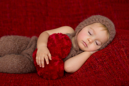 Sweet toddler boy, sleeping with heart toy, cute knitted outfit, isolated, Valentine concept