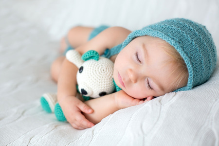 Sweet toddler boy, sleeping with teddy bear toy, cute knitted outfit, isolated