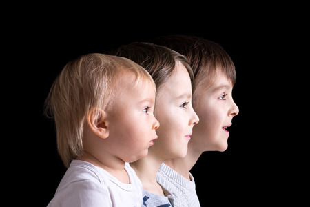Family portrait of three boys, profile picture of them all in a row, isolated on black background, color version Stok Fotoğraf