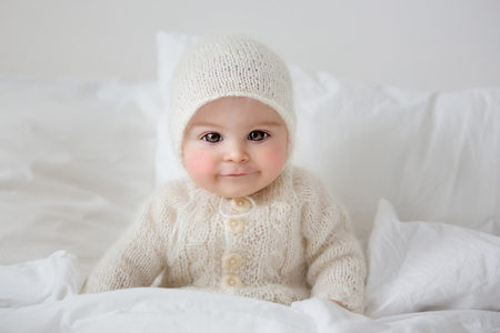 A doll like little cute baby boy, dressed in handmade knitted white teddy bear overall Фото со стока - 116356874