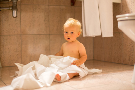 Toddler baby boy, child ripping up with toilet paper in bathroom 写真素材 - 116356886