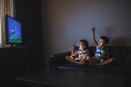 Children, sitting on couch, watching tv at night at home
