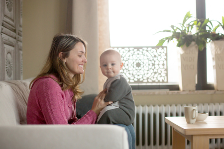 Young mother, holding her toddler boy, breastfeeding him at home, sunny living room