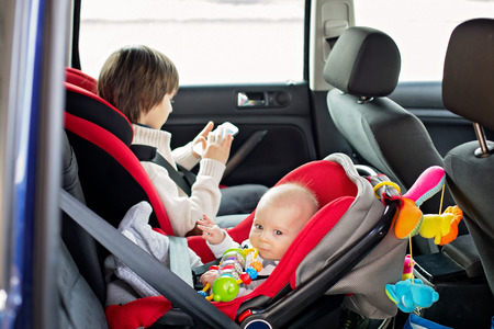 Little baby boy and his older brother, traveling in car seats, going on a holiday, preschool boy playing with mobile phone