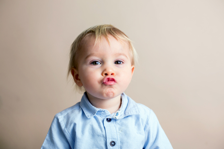 Portrait of cute baby toddler boy, isolated on beige background, child dressed casual