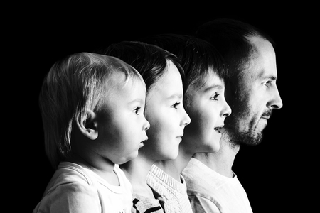 Family portrait of father and three boys, profile picture of them all in a row, isolated on black background, color version