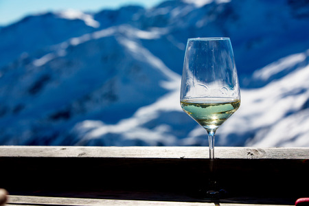 Glass of wine, sitting on rim on a deck, winter landschape behind, snowy mountains of Tyrol Stock Photo