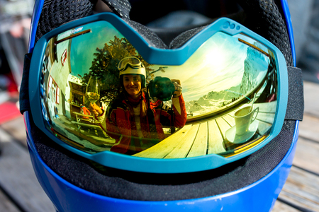 Reflections of woman and children and beautiful mountains on a ski goggles, glass of wine, coffee and cake Stock Photo