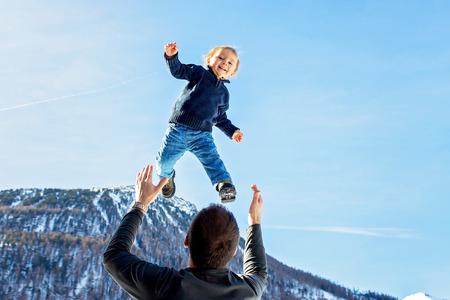 Little toddler boy, flying in the sky, dad throwing him high in the air. Family, enjoying winter view of snowy mountains and frozen lake on a sunny day