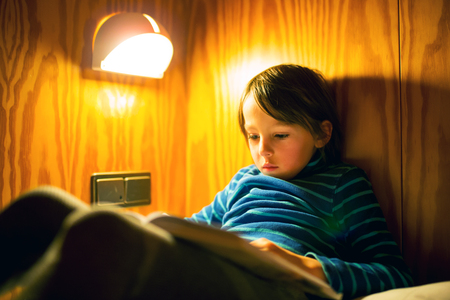 Cute little preschool boy with funny face expression enjoying reading a book lying on the bed with lights at background. Evening home leisure time. Magical world of book Stok Fotoğraf