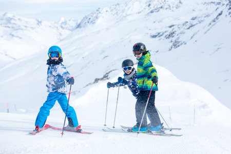 Happy people, children and adults, skiing on a sunny day in Tyrol mountains. Kids having fun while skiing Archivio Fotografico