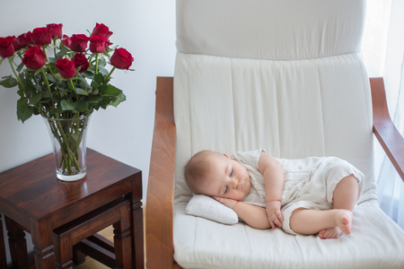 Little cute baby boy, sleeping in armchair with little pillow, cozy toddle, vase with roses on the table next to him Imagens