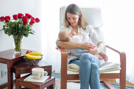 Mother, playing with her toddler boy at home in rocking chair, smiling, breastfeeding Stock fotó