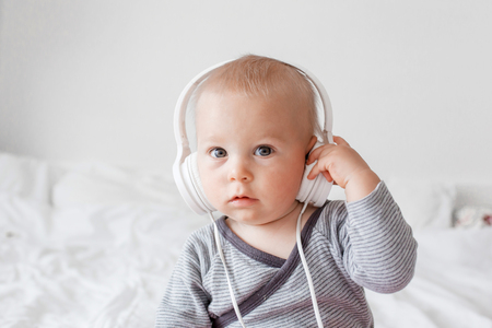 Cute little toddler baby boy listening music with head phones in bed Foto de archivo
