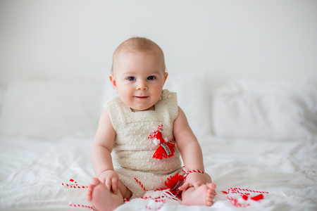 Cute baby toddler boy, playing with white and red bracelets. Martenitsa, white and red strains of yarn, Bulgarian folklore tradition, welcoming spring in March, adornment symbol, wish for good heath Stock Photo