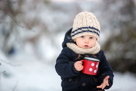 Sweet siblings, children having winter party in snowy forest. Kids friends rest outdoor at nature. Young brothers, boys, drinking tea from thermos. Hot drinks and beverage in cold weather Standard-Bild