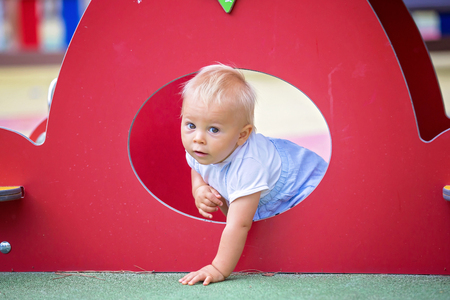 Adorable baby boy, playing with different rides on the playground summertime Stock Photo