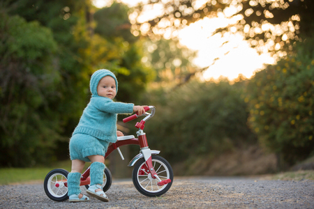 Nettes Kleinkindkind, Junge, spielend mit Dreirad im Hinterhof, Kind reitet Fahrrad auf Sonnenuntergang
