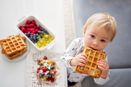 Sweet toddler birthday boy, eating belgian waffle with raspberries, blueberries, coconut and chocolate at home