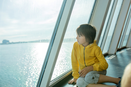 Beautiful children, on board on ferry boat, traveling for a vacation summertime