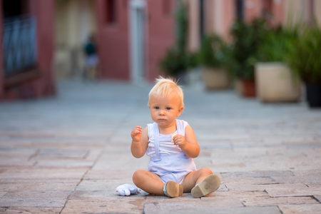 Baby child, boy, sitting on colorful street in the town of Villefrance, French Riviera